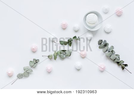 woman light breakfast with marsh-mallow and plant on white table background top view