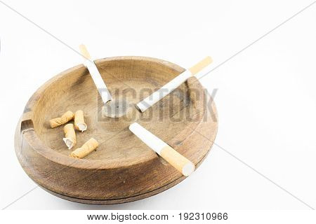 Wooden ashtray with cigar and butts on a white background.