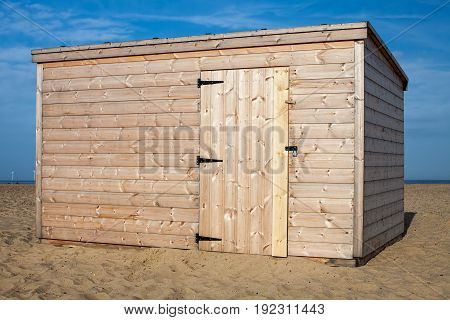 New pinewood shed on the beach. Unpainted storage hut. Cabin on the sand.