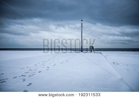 Path to enlightenment. Snow covered beach with footprints leading to an antique lamp post. Cool winter landscape with sea on the horizon.