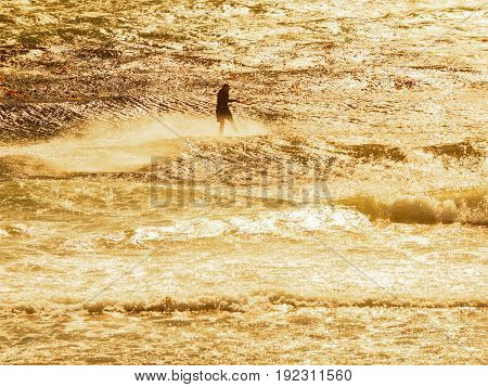 Kite surfer in action on a windy day during sunset