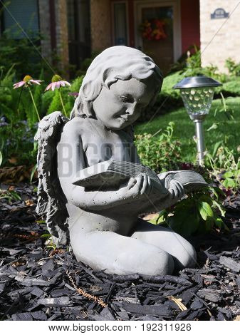 Small kneeling baby girl angel statue in yard reading a book
