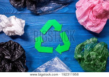 Paper recycle sign with plastic garbage on blue wooden background top view.