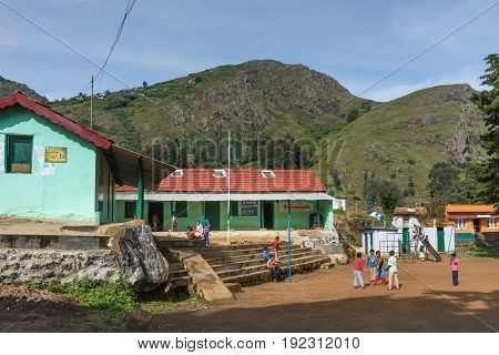 Nilgiri Hills India - October 26 2013: Morning scene with colorfully dressed young kids assembling at the Kallatty elementary school. Highland scenery under blue sky. Red and light green building.