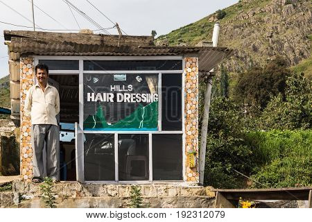 Nilgiri Hills India - October 26 2013: The barber in white dress shirt and gray pants stands waiting for clients in front of his humble shop with highland background.