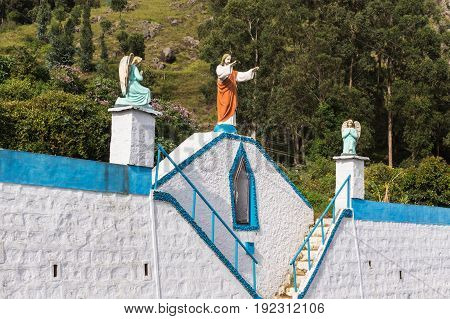 Nilgiri Hills India - October 26 2013: Blue and white steps leading to Catholic church feature statues of Jesus and angels. Highland background.