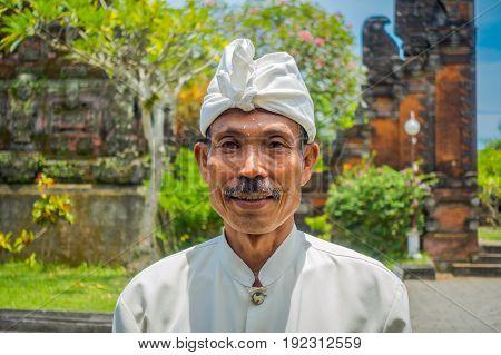 BALI, INDONESIA - MARCH 05, 2017: Unidentified man posing in Pura Ulun Danu Bratan temple on Bali island, Indonesia.