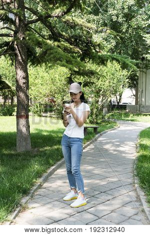 Girl Use A Mobile Phone In The Park