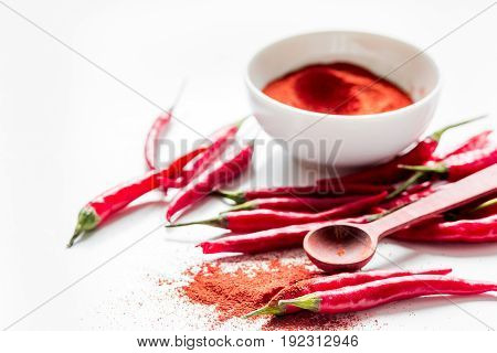 red chili pepper or paprika on white table background close up