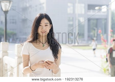 Beautiful Female Students Using Its Ehrs Smartphone In The Campus