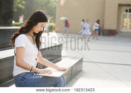 Beautiful Asian College Student With Laptop Sitting On The Steps.