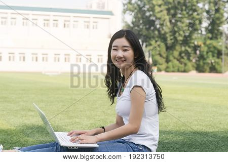 Beautiful Asian College Student With Laptop Sat On The Playground.