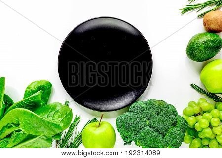green fresh vegetables and fruits and plate for healthy salad on white kitchen table background top view mock up