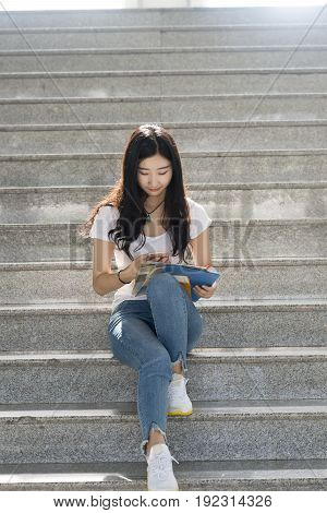 Asian Female Students Using Its Smartphone In The Campus Aisle