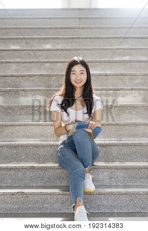 Girl Students Sit On The Steps With Books Smlie