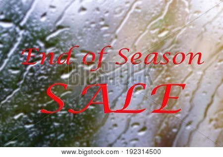 End Of Season Sale Sign On Glass Window With Rain Drops.