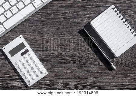 accountant work desk with calculator and notebook for online payment on dark background top view space for text