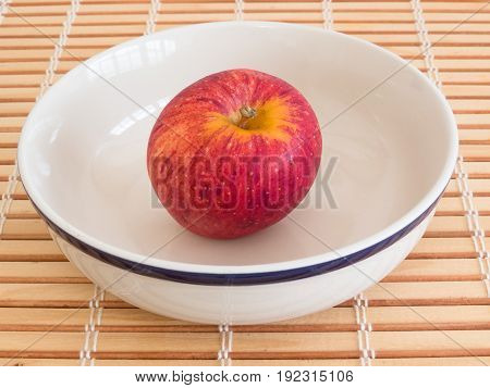 Healthy eating, a fresh red apple inside white bowl on wooden table