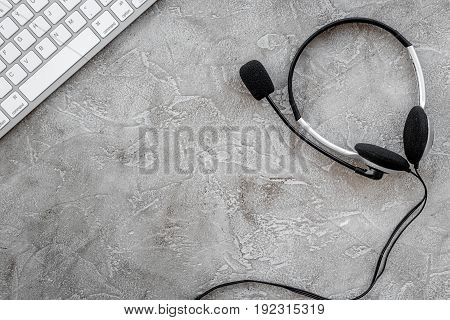manager office desk with contact us set and headset on stone table background top view space for text