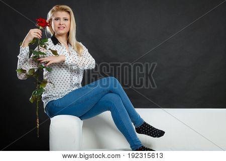 Girl Sitting On Sofa Holds Red Rose, On Dark.
