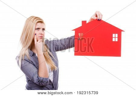 Ownership and property concept. Happy woman holding red paper house thinking about moving to new home.