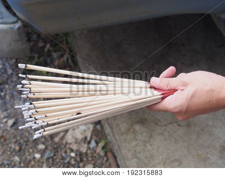 burning incense sticks holding on a hand with waving smoking