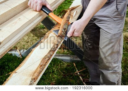 Stripping the planks from the bark with an axe