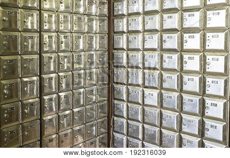 Corner full of rows of old shiny metal post office boxes