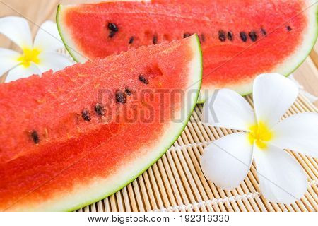 watermelon with plumeria flowers on the table