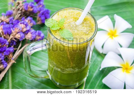Green apple juice in the glass and flowers on banana leaf