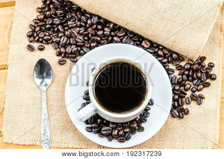 Coffee cup with coffee beans on sack on wooden table background.