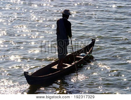Ubein Rower. A local in his canoe on the river at the U-Bein bridge in Myanmar