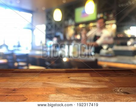 Empty wooden table top with blurred bar and bartender mixing beverage on background