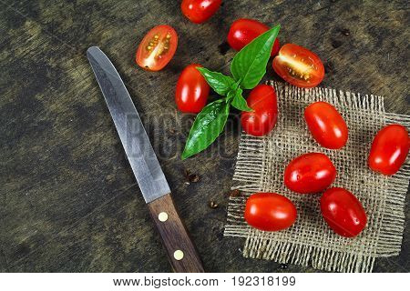 Cherry tomatoes with basil leaf on a white background