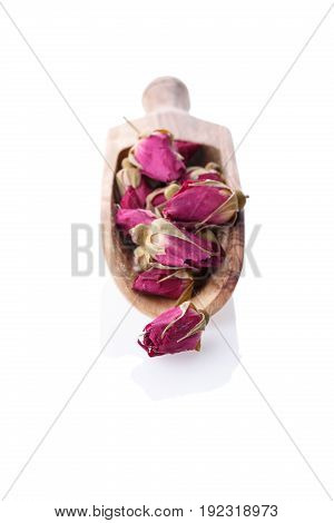 Close-up of dry red rose buds on wooden scoop. Healthy herbal tea Isolated on white background. Selective focus.