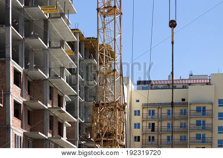 Fragment of building and tower crane in the courtyard against the background of unfinished buildings