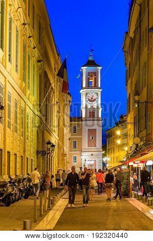 Nice France - May 27 2017: People walking in the streets of the Old Town fille with restaurants and cafes. Clock Tower and a sliver of the new moon in the background