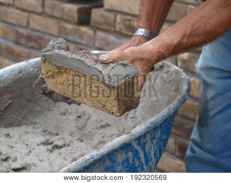 A brick mason works his craft. He is not using  a mortar board because of how close the work is to his mortar.