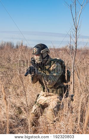 aiming, airsoft player with gun, helmet and bulletproof vest