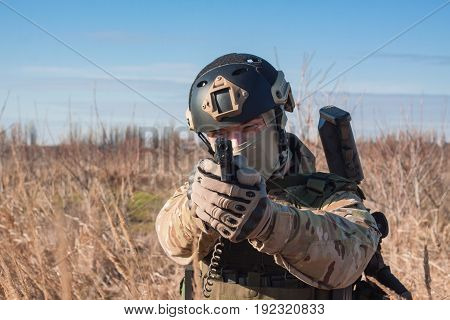 soldier in nato uniform posing in fields with black handgun