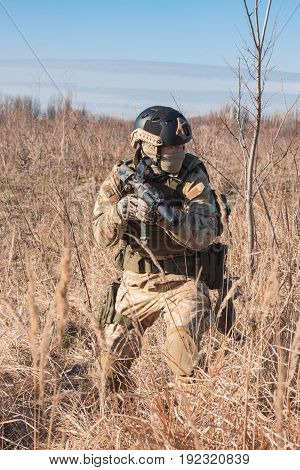 Close up picture of airsoft soldier with a combat rifle in fields