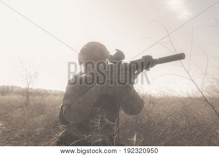 Airsoft soldiers in uniform on the battlefield in fog