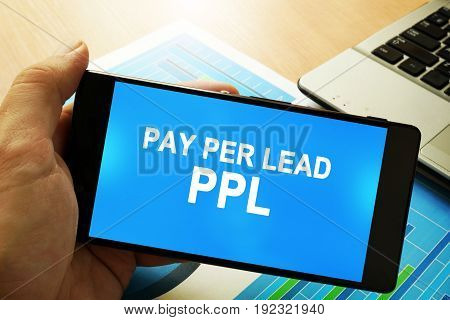 Hand holding smartphone with words Pay per lead PPL.