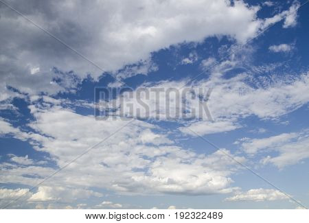 Dark blue summer sky background white clouds flying in the stormy sky
