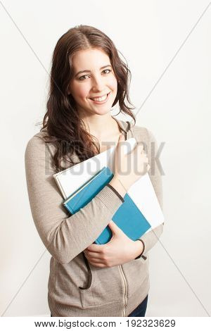 beautiful smiling young woman with long dark hair holding books