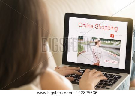 Woman lying on sofa with laptop pc visits apparel store web page in Internet. Female customer shopping trendy clothes. Girl buying elegant wear on seasonal sale online. Close up view over the shoulder