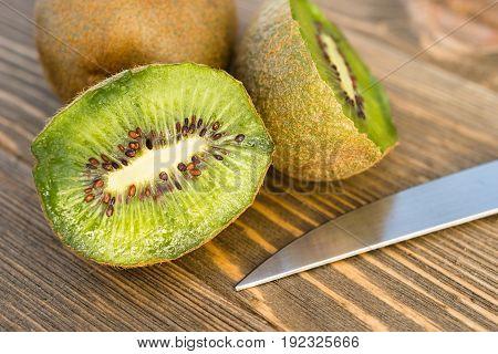Two Kiwi Fruits sit on the cutting board