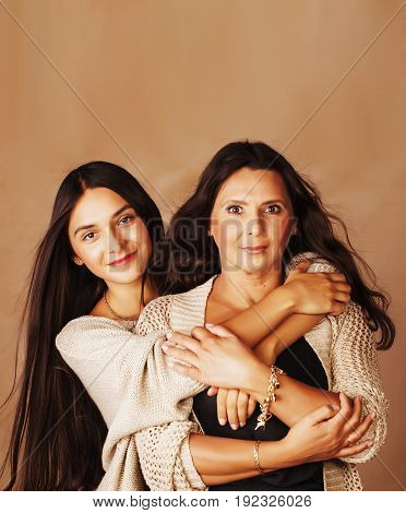cute pretty teen daughter with mature mother hugging, fashion style brunette makeup close up tann mulattos, warm colors close up