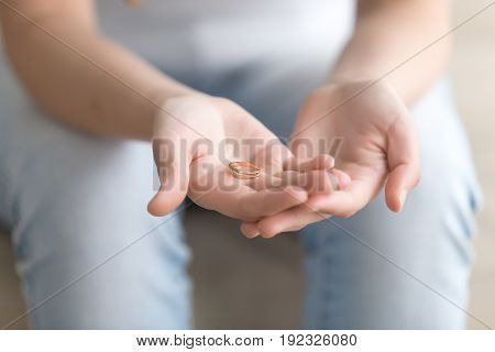 Close up image of golden ring on young female palms. Woman thinking about divorce while holding wedding ring in hands. Marriage proposal, doubts after engagement concept. Family values and breakup