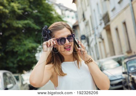 Young fashionable woman using smart phone outdoors.